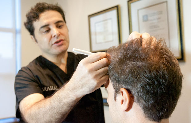 Picture of Dr. Rahal drawing a hairline on a patient.