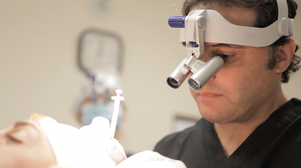 A picture of Dr. Rahal performing a hair transplant procedure using state-of-the-art technology.