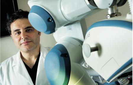 A picture of Dr. Hussain Rahal standing beside the ARTAS Robotic System.